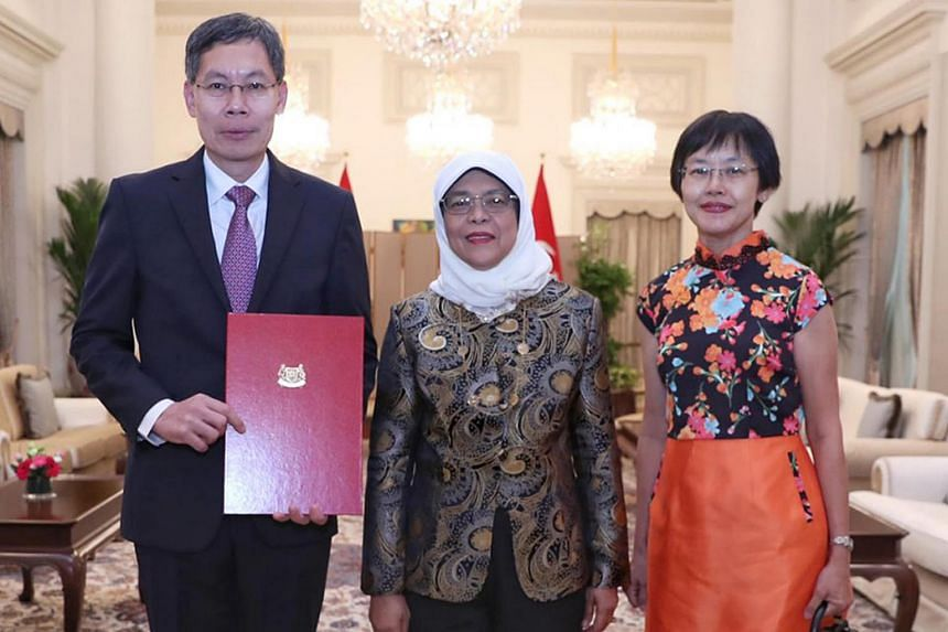 Former transport minister Lui Tuck Yew receiving his letter of credence as Ambassador-designate to China from President Halimah Yacob at the Istana. With them is Ms Teng Soo Fen, Mr Lui's wife.