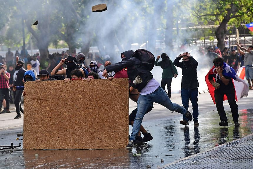 Demonstrators clashing with riot police in Santiago on Tuesday. Chile's decision to cancel the Apec summit highlights the depth of trouble facing the nation which has seen the worst unrest in a generation. Until just two days ago, the government had