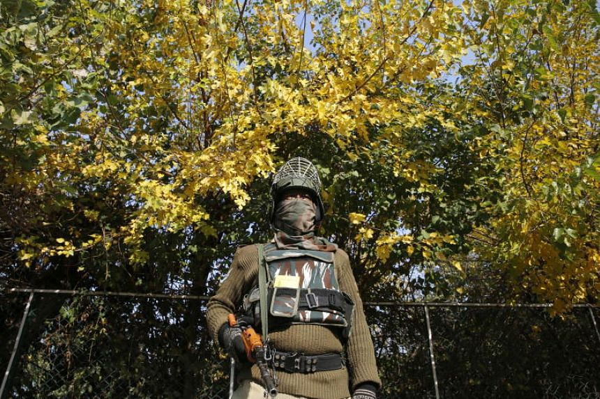 An Indian paramilitary soldier stands guard on the side of a road leading to Raj Bhawan where an oath ceremony takes place in Srinagar, India, on Oct 31, 2019.