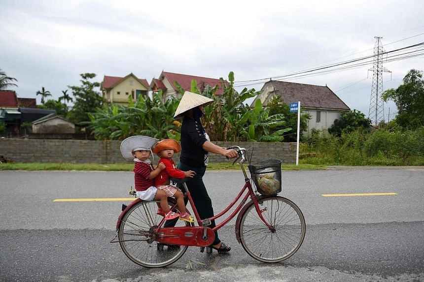 A woman carries children on a bicycle in Nghe An province where families of missing Vietnamese migrants reside, on Oct 29, 2019.