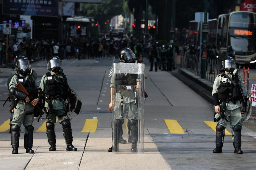 Police officers stand guard during an anti-government protest in Hong Kong's tourism district of Tsim Sha Tsui, on Oct 27, 2019.