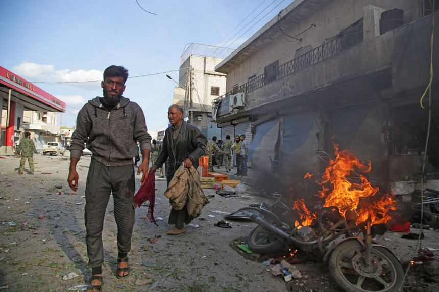 Syrians walk past a burning motorcycle at the site of a car bomb explosion in Tel Abyad.
