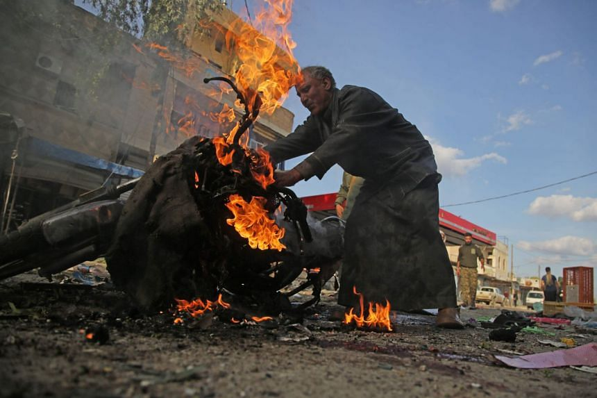 A Syrian man stands next to a burning motorcycle at the site of a car bomb explosion in Tel Abyad.