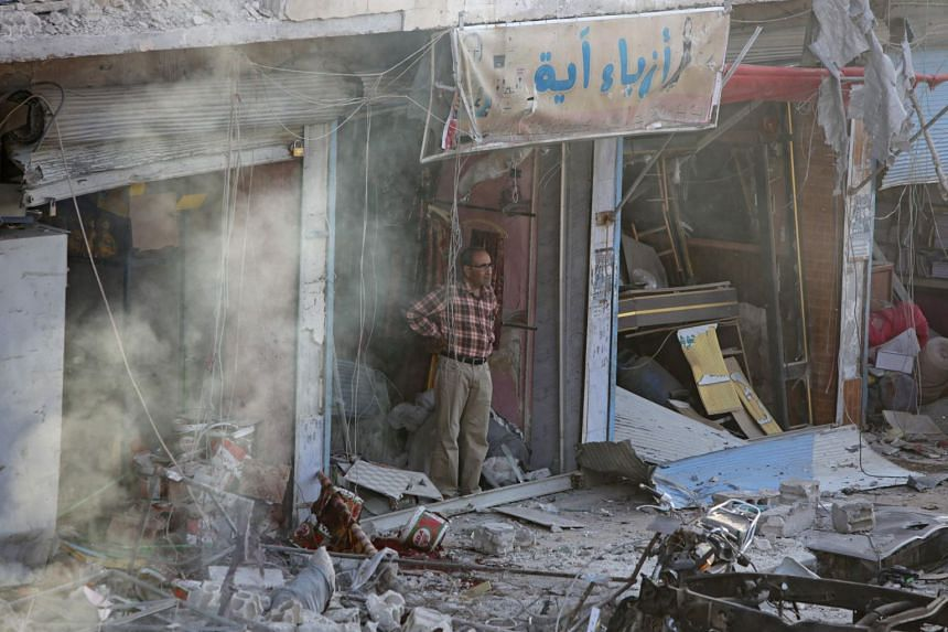 A Syrian man inspects the site of a car bomb explosion in Tel Abyad.