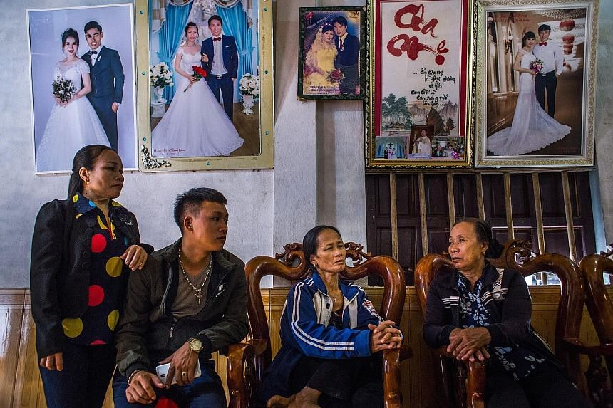 Above: British police say brothers Christopher (left) and Ronan Hughes are crucial to their inquiries. Right: Relatives comforting Madam Nguyen Thi Huan (third from left), the mother of 20-year-old Nguyen Dinh Luong - said to be among the 39 people f