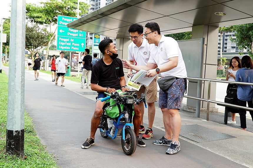 Coraltree Residents Network chairman Andy Ho (centre) and Parc Terraces Residents Network chairman John Yap talking to a personal mobility device user in Punggol about using the device safely and responsibly, as part of the Active Mobility Patrol sch