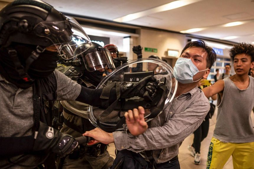 Police try to detain a man in Sha Tin, Hong Kong, on Nov 3, 2019.