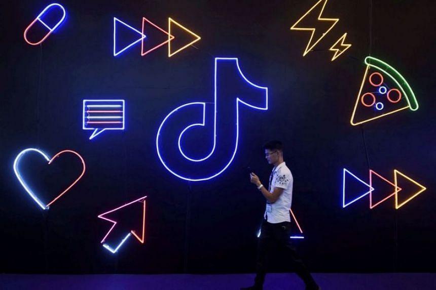 A man holding a phone walks past a sign of Chinese company ByteDance's app TikTok in China.