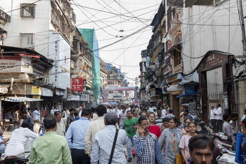 In a photo taken on Oct 16, pedestrians walk past stores in the Zaveri Bazaar, in Mumbai, India.
