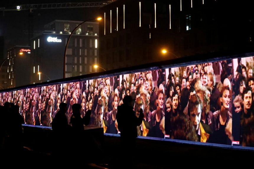 Historic video footage from the fall of the Berlin Wall is projected during a rehearsal with 3D video beamers on the East Side Gallery, the largest remaining part of the former Berlin Wall, in Berlin, Germany, on Nov 3, 2019.