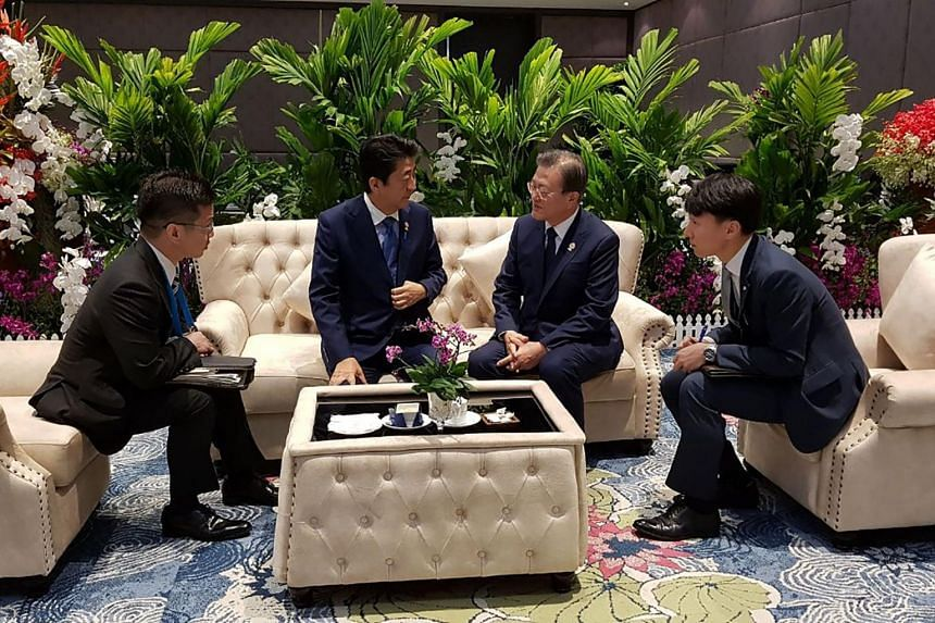 South Korea's President Moon Jae-in (second from right) talking with Japan's Prime Minister Shinzo Abe (second from left) during their meeting in Bangkok, on the sidelines of the 35th Asean Summit, on Nov 4, 2019.