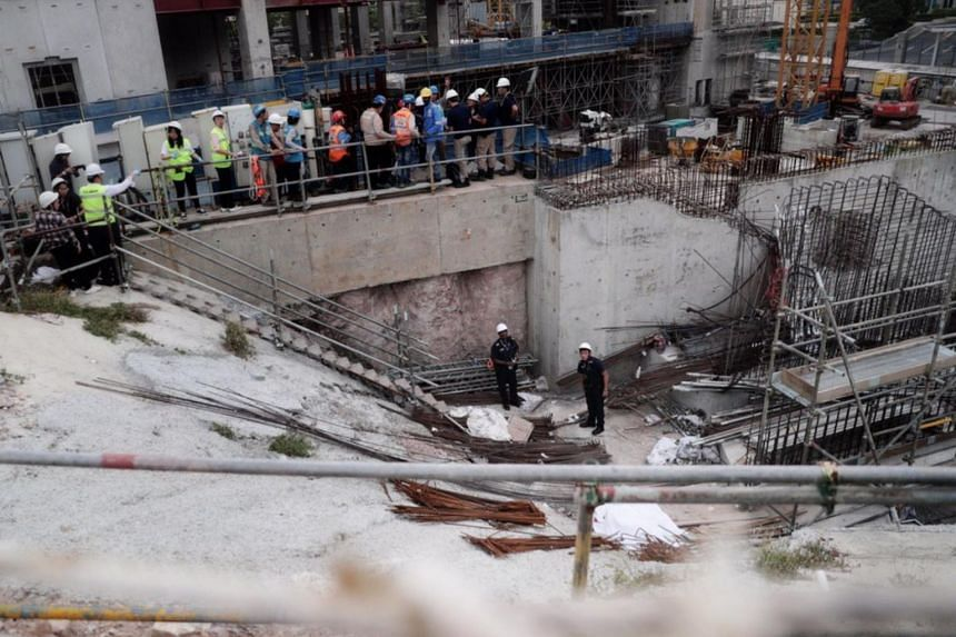 A body covered in white cloth (bottom right) at the construction site in Novena where a crane had collapsed. Workers at the site said the dead man was an Indian national.