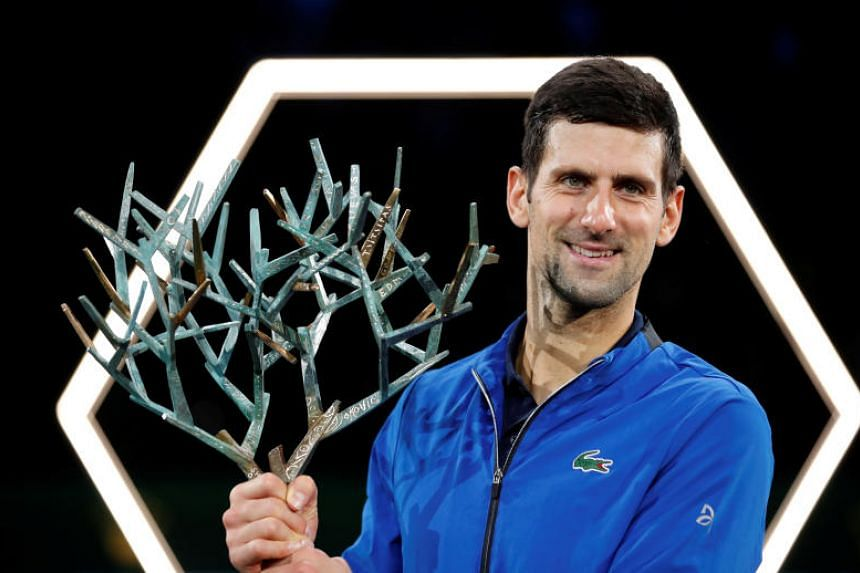 Serbia's Novak Djokovic celebrates with the trophy after winning the Paris Masters at the AccorHotels Arena in Paris on Nov 3, 2019.