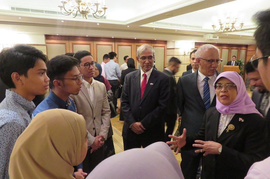 President Halimah Yacob chatting with students during the reception, accompanied by her husband Mr Mohamed Abdullah Alhabshee (in blue tie) and Mr Zainul Abidin Rasheed (red tie), Singapore's non-resident ambassador to Kuwait.