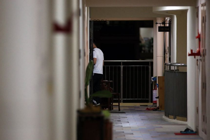 In a photo taken on Sept 27, 2017, a customer is seen entering a four-room HDB flat where illegal prostitution is taking place. Key changes to the Women's Charter include the expansion of the definition of a brothel.