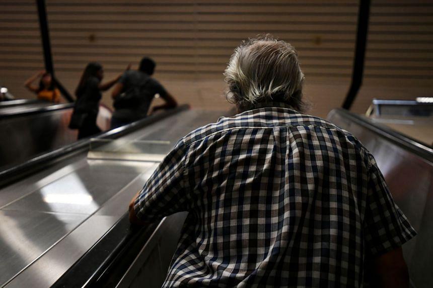 An elderly man on an escalator at Ang Mo Kio MRT station.