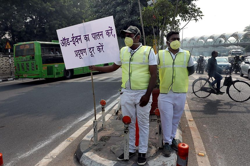 """Indian civil defence volunteers holding placards in Hindi which read """"Follow the odd and even scheme and make Delhi pollution free"""" yesterday - the first day of the implementation of the city's odd-even scheme for vehicles."""