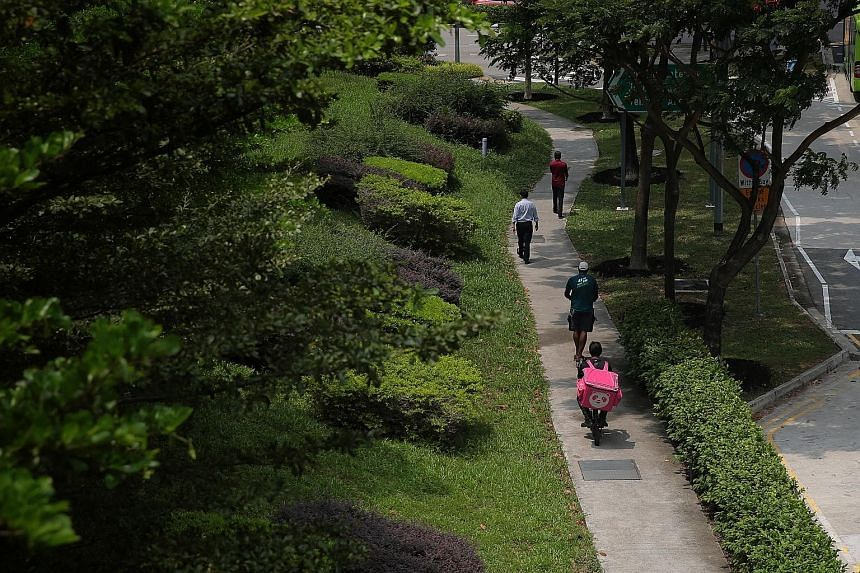 E-scooter riders on a footpath in Jurong East yesterday. There are about 7,000 food delivery riders in Singapore who use e-scooters, the majority believed to be working for Grab.