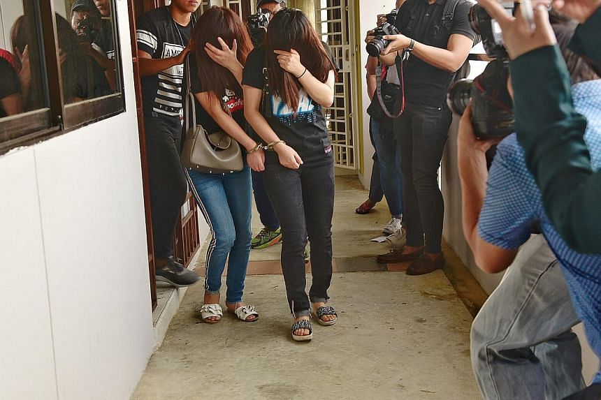 Women arrested in a raid on a Woodlands flat last year for alleged involvement in vice-related activities. Between 2015 and last year, seven in 10 foreign women nabbed for online vice were providing sexual services in residential estates. ST FILE PHO