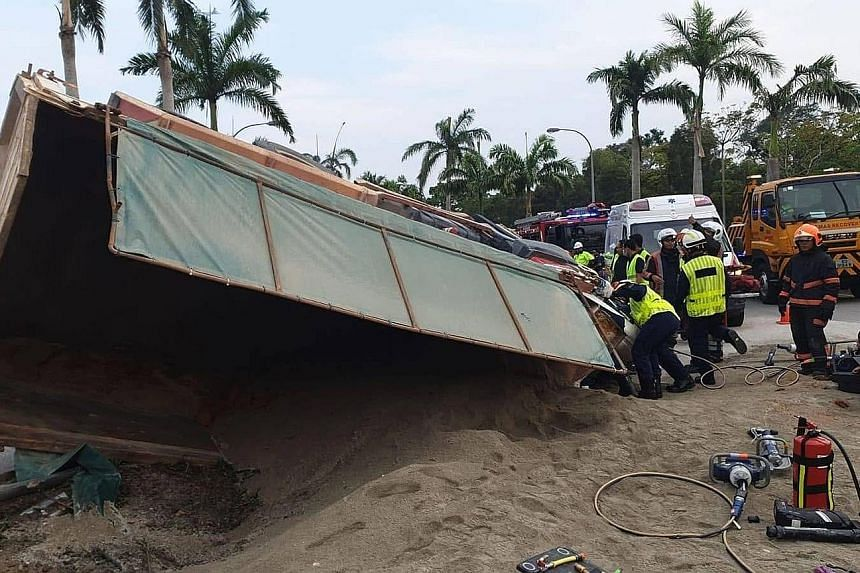 The driver's side of the tipper truck was crushed when the vehicle landed in a drain. PHOTO: SINGAPORE CIVIL DEFENCE FORCE
