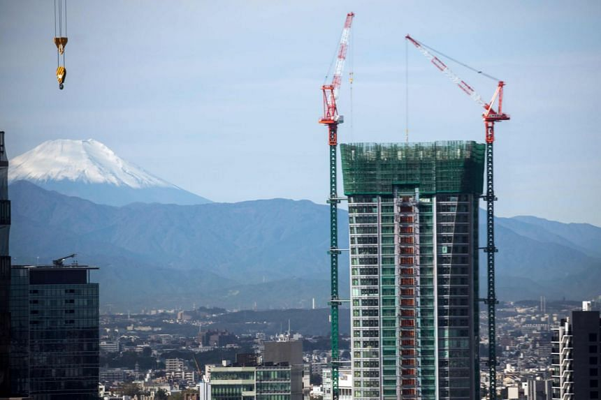 A photo of Mount Fuji is seen from Tokyo behind construction sites of new high-rise buildings in the Japanese capital on Oct 26, 2019. The industry sees artificial intelligence and robots as a way to future-proof and close the labour gap.