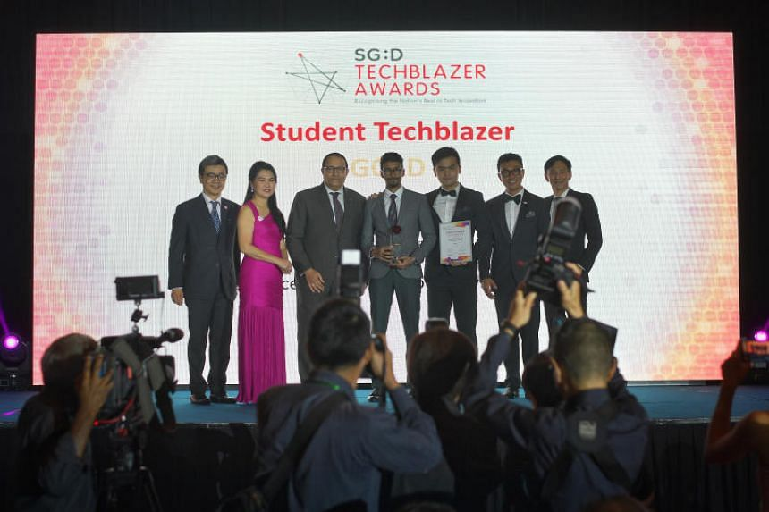 Minister for Communications and Information S. Iswaran (third from left) presenting the award for the Student Techblazer category of the Singapore Digital Techblazer Awards to Aravind Kandiah and Charles Wong (both centre) on Nov 5, 2019.