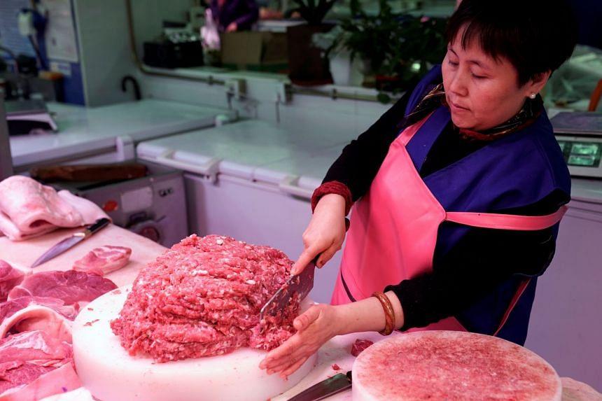 A vendor prepares pork for sale at a market in Beijing.