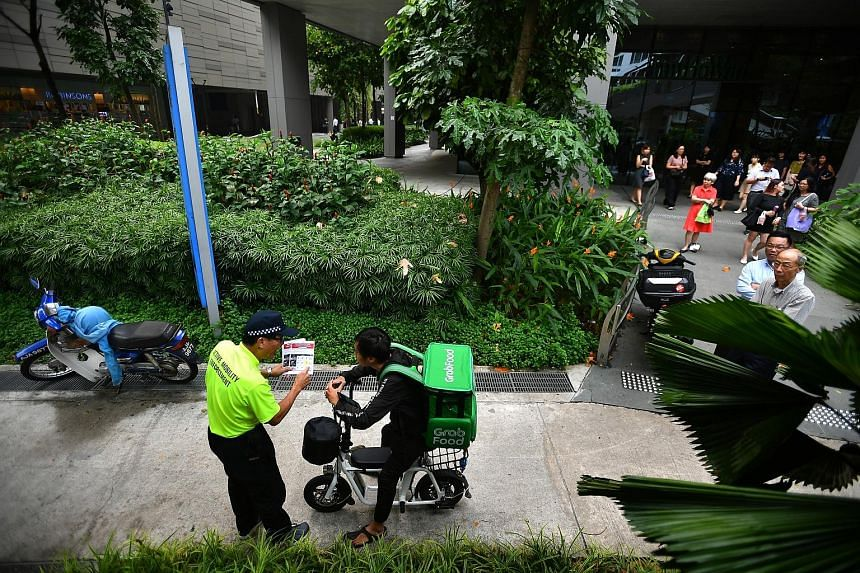 """An enforcement officer warning a food delivery rider on his electric scooter on a footpath outside Westgate mall yesterday. The LTA said it will issue warnings to errant riders till Dec 31, but will take """"strict enforcement action"""" in serious cases."""