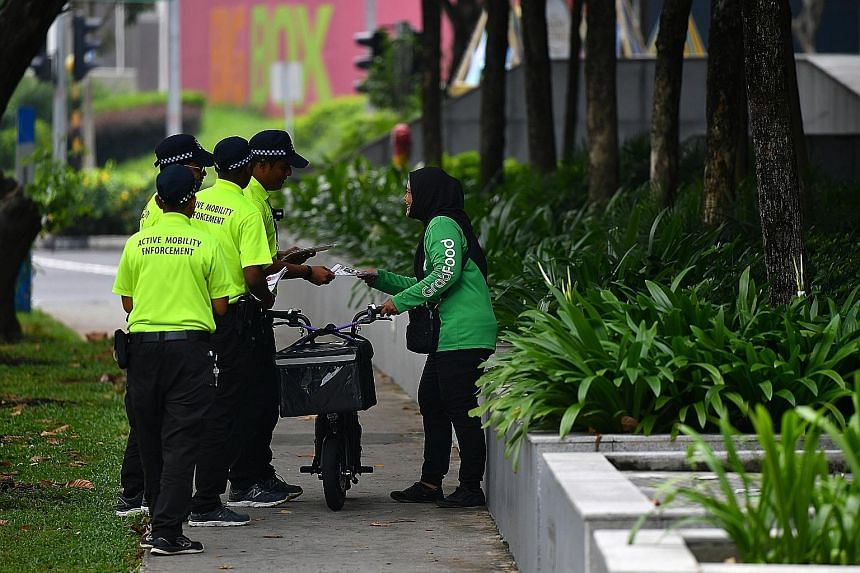 Food delivery riders seen using their electric scooters on the footpath outside Jem shopping mall yesterday (above and below left) were approached by enforcement officers and given warnings. The flier being given out by LTA enforcement officers to in
