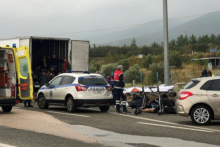Some of the 41 migrants lying on the road while others remained inside the refrigerated truck during a routine police check near Xanthi city in Greece on Monday. Police arrested the driver and took him and the migrants to a nearby police station for