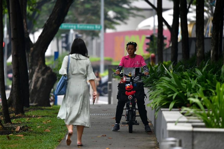 Foodpanda delivery rider Yeo Ming Fong, 31, riding an electric scooter on the footpath outside Jem shopping mall, on Nov 5, 2019.