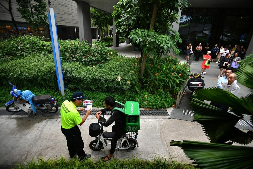 An Active Mobility Enforcement officer approaching GrabFood delivery rider Adrin Lim, 27, outside Westgate mall, on Nov 5, 2019.