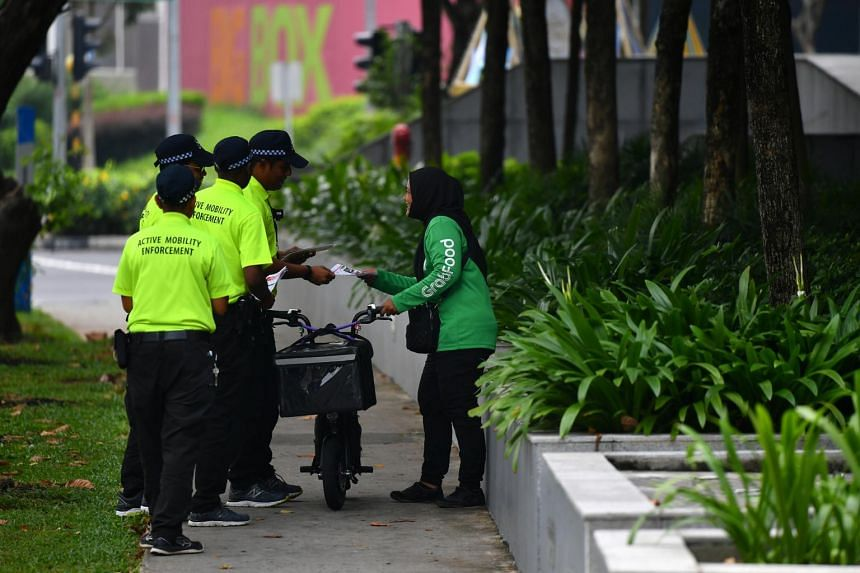 Active Mobility Enforcement officers approaching a GrabFood delivery rider riding with her electric scooter on the footpath outside Jem shopping mall, on Nov 5, 2019.