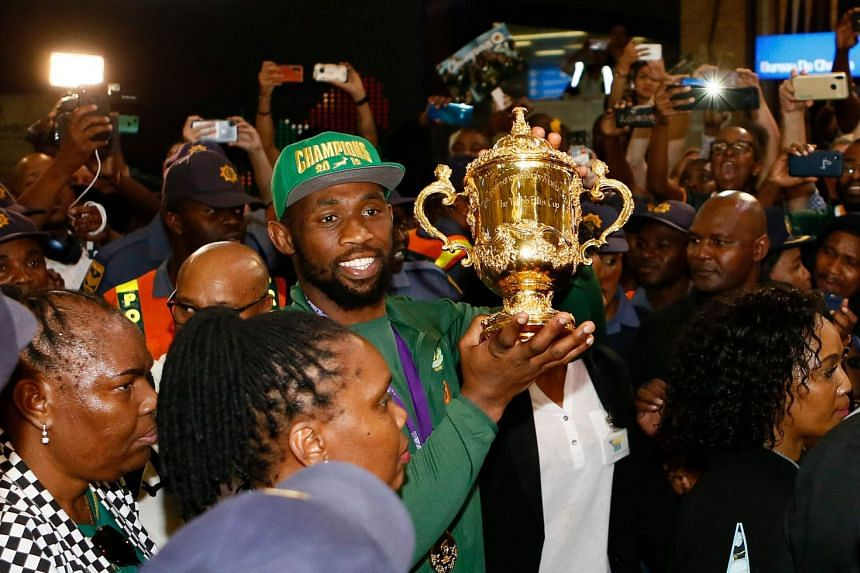 Springboks captain Siya Kolisi (centre) carries the Web Ellis Cup through the crowd upon the team's arrival at the OR Tambo International Airport.