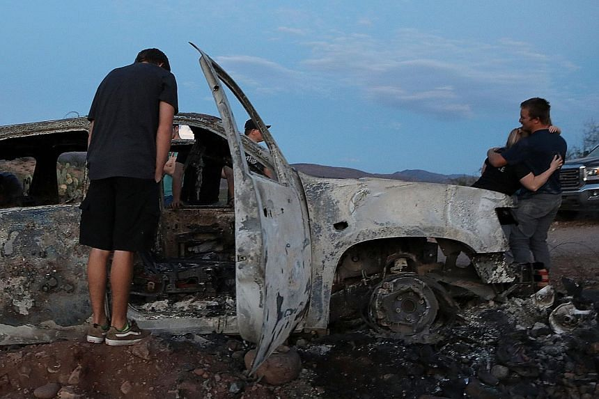 Relatives at a burnt car of the US family who were ambushed in Mexico. At least nine members of the family, including a pair of eight-month-old twins, were killed.