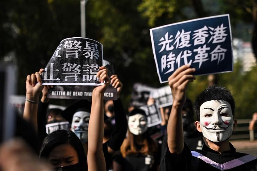 University students wear Guy Fawkes masks, popularised by the V For Vendetta comic book film, during an anti-government protest at their graduation ceremony at the Chinese University of Hong Kong on Nov 7, 2019.