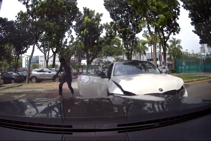A screengrab of a dashcam video showing the driver of a BMW coupe abandoning his BMW at a carpark.