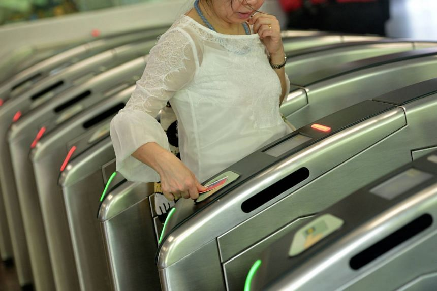 A commuter tapping a card at a fare gate at Ang Mo Kio MRT Station. Commuters can start paying for rides with Nets contactless bank cards from Nov 16.