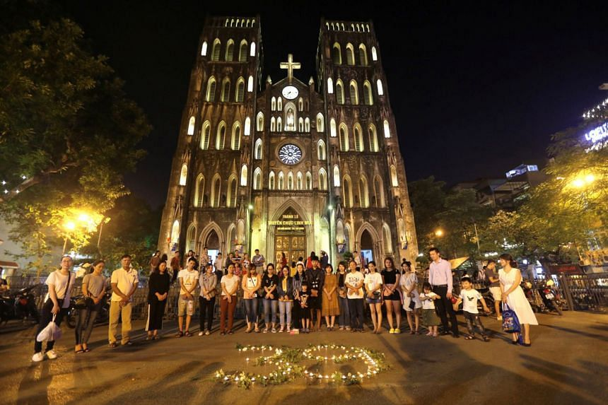 In a photo taken on Oct 27, 2019, people light candles to pray for the 39 people found dead in the back of a truck near London, in front of Hanoi Cathedral in Hanoi, Vietnam.