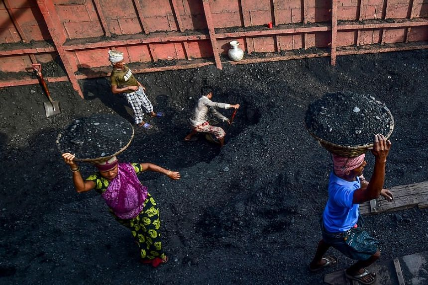 Labourers unload coal from a cargo ship in Gabtoli on the outskirts of Dhaka, Bangladesh, on Nov 6, 2019.