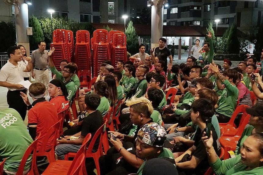 Minister for Social and Family Development Desmond Lee meeting a group of food delivery riders last night at his Meet-the-People Session in Jurong Spring. ST PHOTO: KHALID BABA