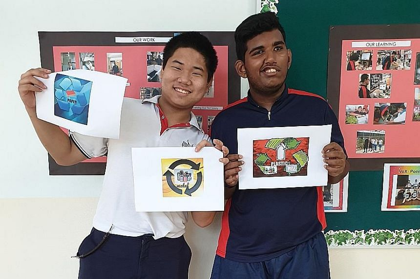 Dunman High School's Arthur Yeo (left) and Movement for the Intellectually Disabled of Singapore Towner Gardens School's Mohd Shameer Mohd Rafiq with recycling logos they designed.