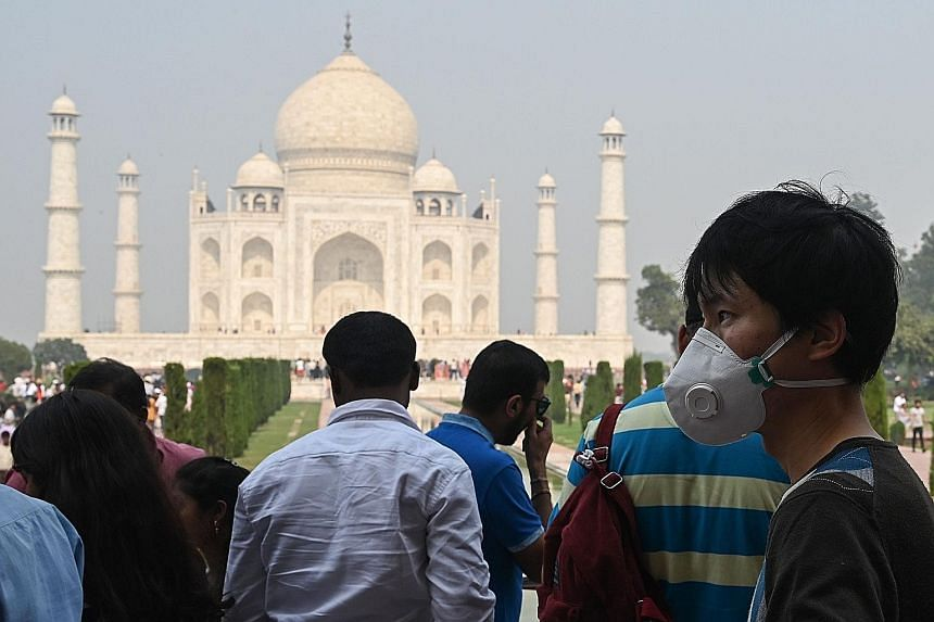 A tourist at the Taj Mahal in Agra wearing a face mask to protect against air pollution. Analysts say India's plans to tackle the problem suffer from lackadaisical enforcement and lack of coordination. There are few penalties, and little transparency