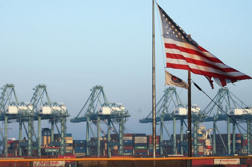 A US flag flies with shipping containers stacked at the Port of Los Angeles in the background, which is the nation's busiest container port, on Nov 7 in San Pedro, California.
