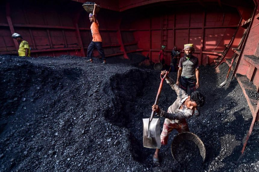 In a photo from Nov 6, 2019, labourers unload coal from a cargo ship in Gabtoli on the outskirts of Dhaka, Bangladesh.