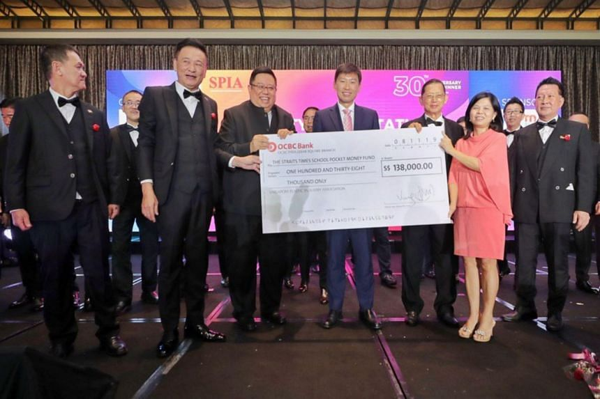 SPIA President Ronald Lim (second from left) and guests present a mock cheque of $138,000 to The Straits Times School Pocket Money Fund General Manager Tan Bee Heong (in pink) in support of ChildAid 2019 with Senior Minister of State for Trade and In