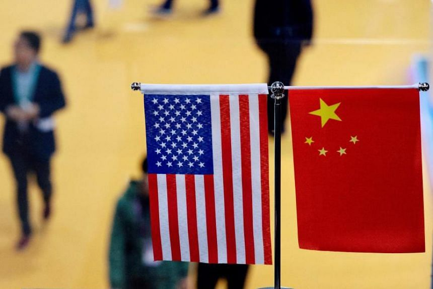 A photo of a Chinese and US flag at a booth during the first China International Import Expo in Shanghai on Nov 6, 2018. Experts said the announcement that existing tariffs would be rolled back in stages was a positive development.