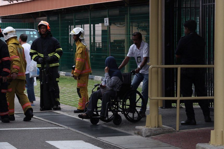 A woman on a wheelchair being led to an ambulance at Tanah Merah ferry terminal, on Nov 8, 2011.