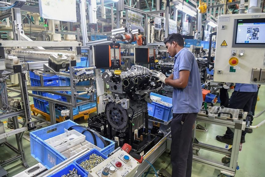 A worker assembles the engine of a car at a manufacturing facility in Ranjangaon, Mumbai.