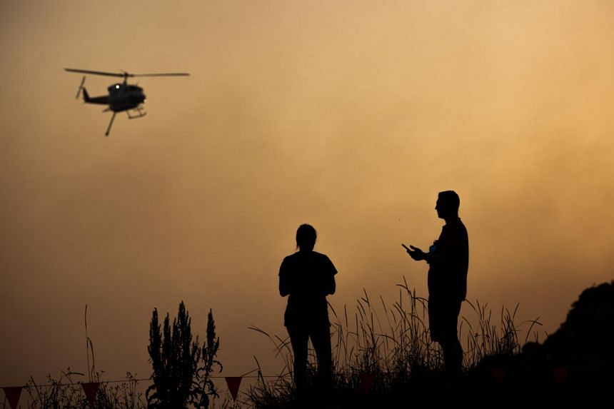 A water bombing helicopter flies over a bushfire as residents look on, in Forster, New South Wales, Australia, on Nov 7, 2019.